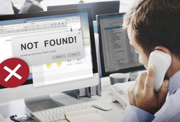 Geschäftsmann telefoniert an seinem Schreibtisch, auf dem Monitor erscheint die Fehlermeldung: Not Found!