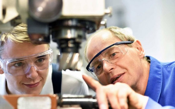 Ein Ausbilder erklärt einem Auszubildenden eine Maschine, beide tragen eine Schutzbrille