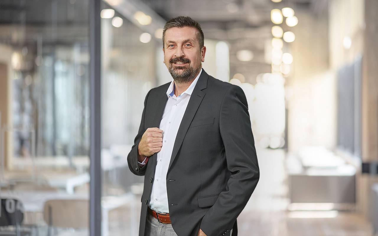 Vertriebsleiter Klaus Wadel, stehend mit einer Hand am Revers, die andere in der Hosentasche