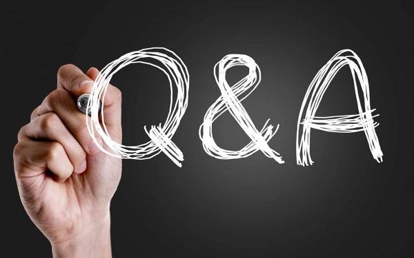 Eine Hand schreibt mit einem Stift Q & A