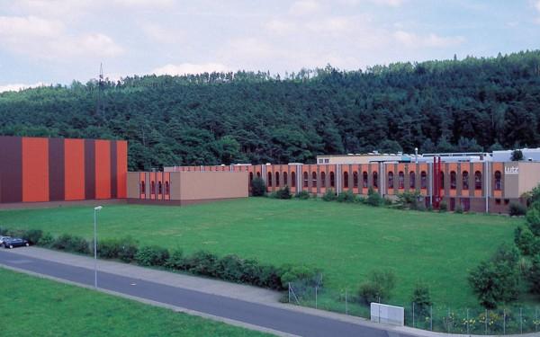 Produktionsgebäude mit Hochregallager des Unternehmens am Rand eines kleinen Waldes mit Rundbogenfenstern